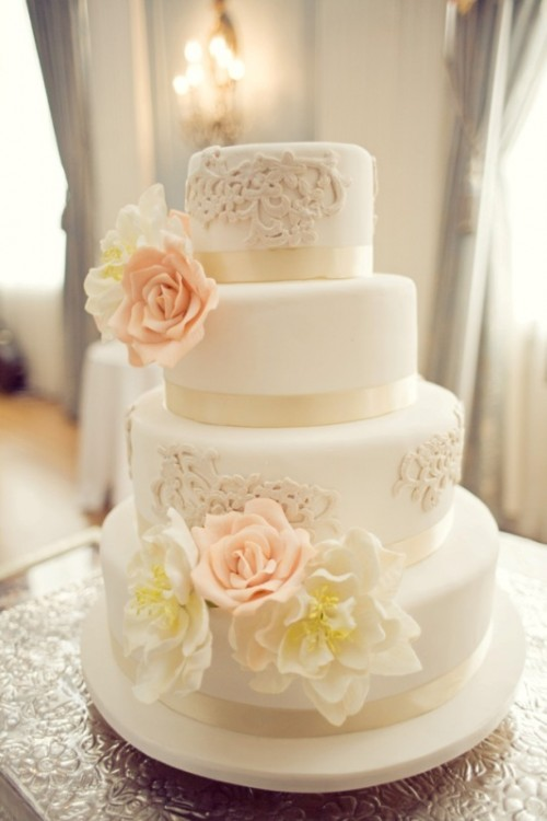 a white wedding cake decorated with tan lace and sugar blooms in pink and white is a cool idea to rock