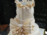 an unusual wedding cake with lace, buttons, oversized flowers and bows, plus a terrarium with a little tree on top