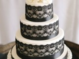 a white wedding cake decorated with black lace and ribbons and sugar flowers on top plus branches