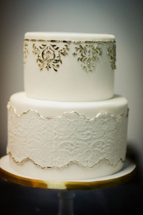 a beautiful white wedding cake decorated with white lace with a gold edge, gold decor on the upper tier