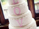 a neutral lace wedding cake with pink letters and pink sugar blooms on top is a cute idea with the main word