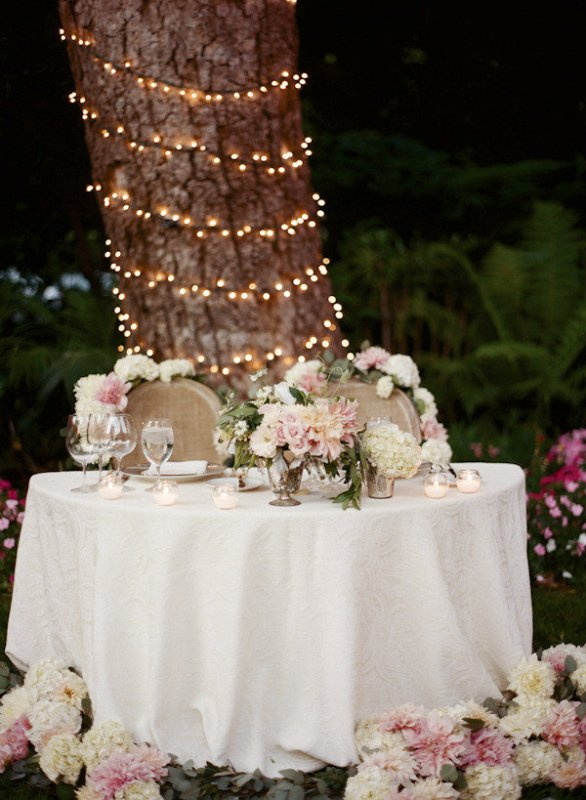 the table is decorated with lush pink and white blooms, the so are the chairs and the same blooms surround the table