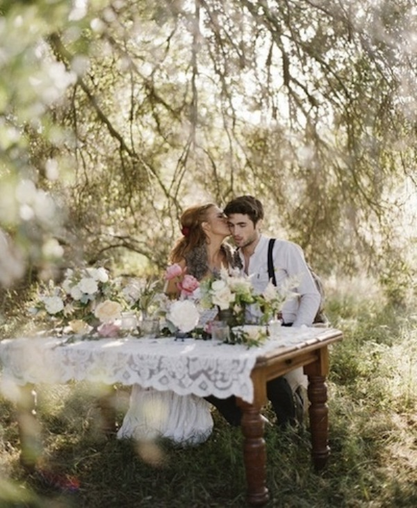 a white lace tablecloth and several arrangements in pink and white create a lush and romantic sweetheart table