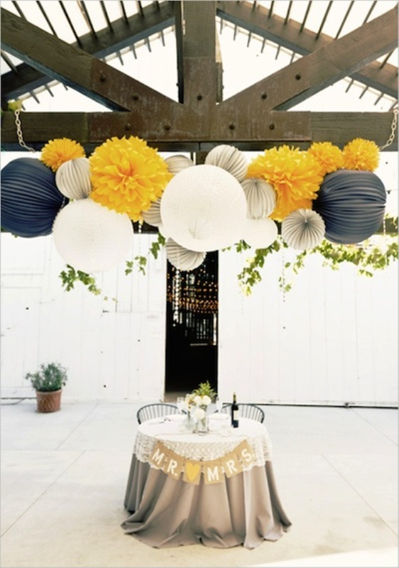 the sweetheart table accented with a burlap bunting and colorful paper balls over the table