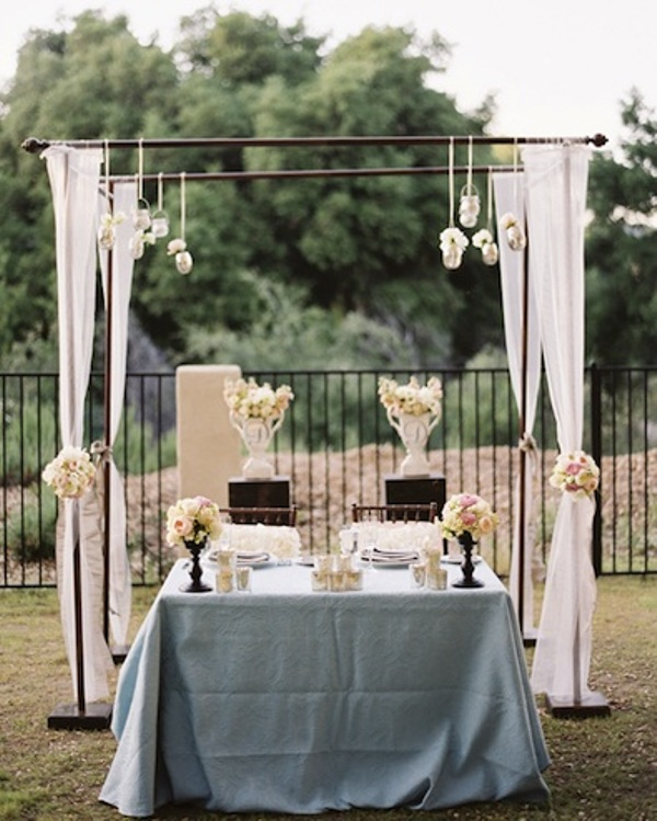 a sweetheart table decorated with lush white florals, candles and with a wedding arch with fabric, blooms and suspended candles