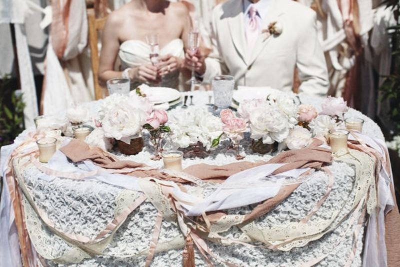 a lace tablecloth, lots of ribbons that match in color and a table runner of white and pink blooms plus candles