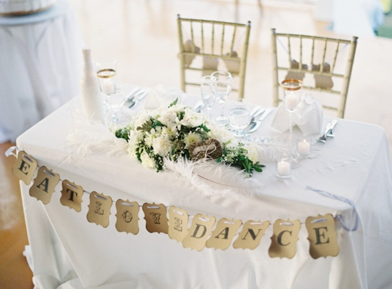 a paper bunting, candles and a lush floral centerpiece will make your sweetheart table stand out but not too much