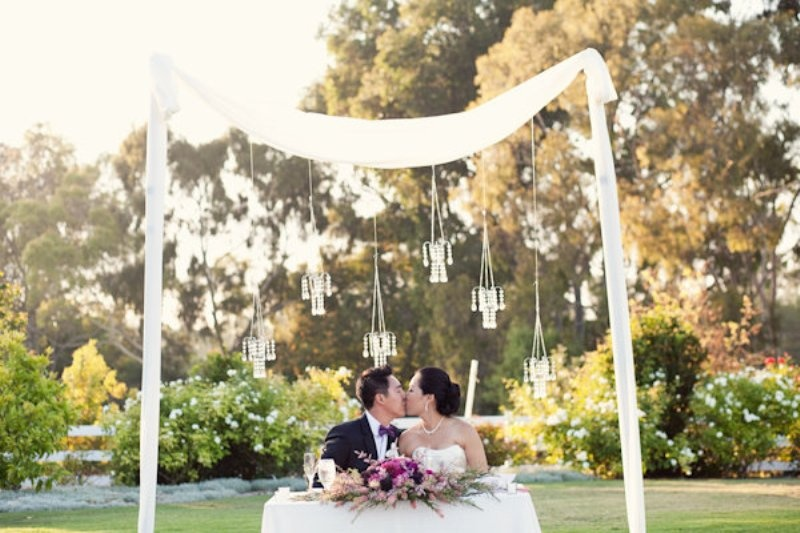 a lush and bright floral centerpiece and a wedding arch with fabric and suspended candles over the table