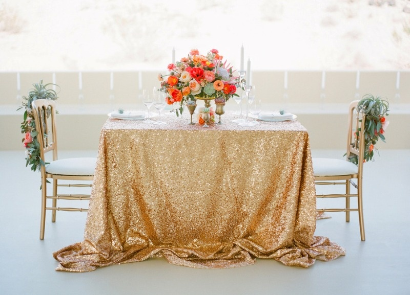a gold sequin tablecloth, a lush and bold floral centerpiece and chairs decorated with bright blooms and air plants will highlight your space