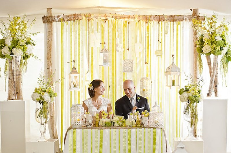 an arch with ribbons and candles and candle lanterns plus some cages, florals and branches around the sweetheart table