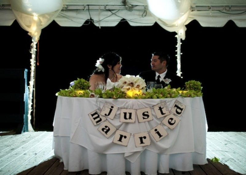 a paper bunting, candles, greenery garlands and a white florla centerpiece to highlight the sweetheart table