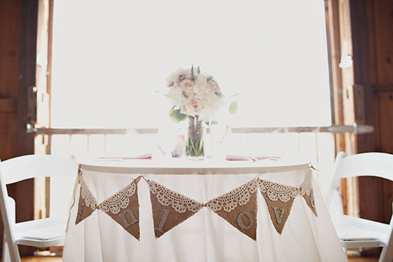 a simple cardboard and lace bunting and a tender floral centerpiece to accent the swetheart table