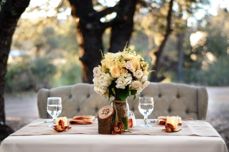 a lush floral centerpiece, candles, fall leaves and a rustic table number for an accent