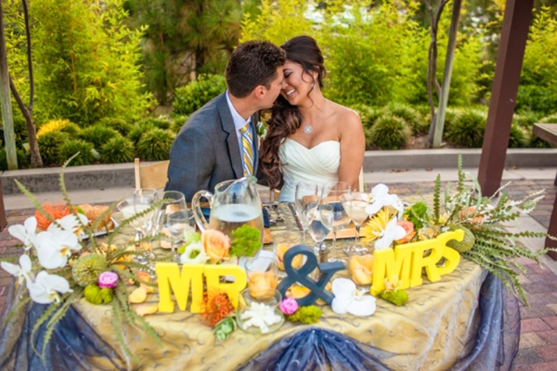 letters, an ampersand, greenery, moss and bright blooms for decorating the sweetheart table in a colorful way