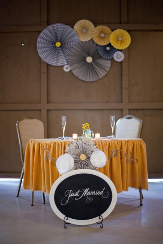 a bright tablecloth, contrasting paper fans, a chalkboard sign and paper fans on the wall behind the table