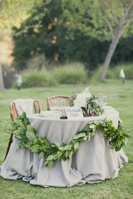 a greenery garland and a lush white blooms and greenery centerpiece to highlight the sweetheart table