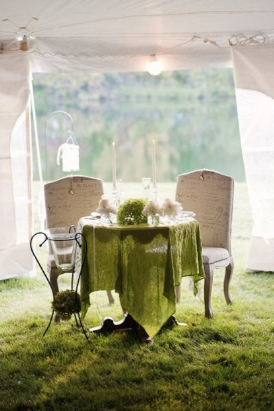 a sweetheart table topped with a green asymmetrical tablecloth, greenery, neutral blooms and an oversized candle holder next to the table