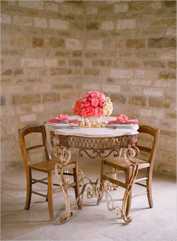 a lush pink floral centerpiece, matching napkins and floral napkin rings and candles in the center of the table