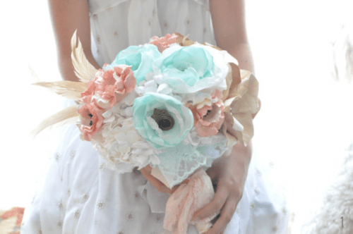 a lovely pastel wedding bouquet of mint, coral and white fabric blooms and feathers for a romantic bride