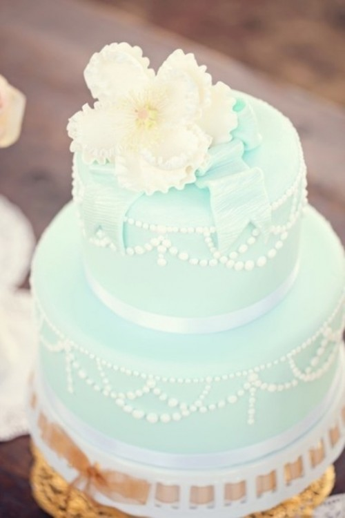 a chic mint green wedding cake with white beading and edible ribbons plus white blooms on top