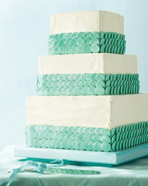 a square textural white wedding cake with mint green scales for decor looks cool, fresh and summer-like