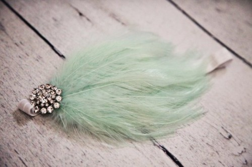 a mint wedding accessory of a feather and a vintage brooch is a cool and cute idea