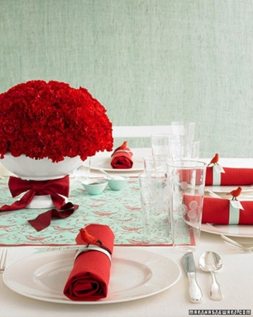 a bright mint and red wedding tablescape with red textiles, bright red blooms and a red rose centerpiece