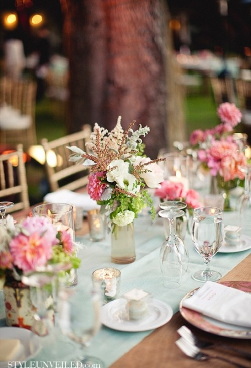 a light mint green wedding table runner looks cool and fresh with bright pink blooms that are centerpieces