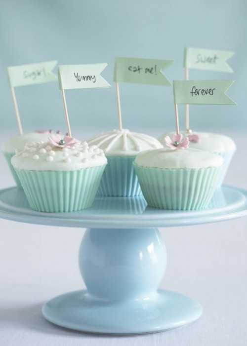 cute cupcakes with icing, edible beads and flowers in mint green liners and with fun toppers