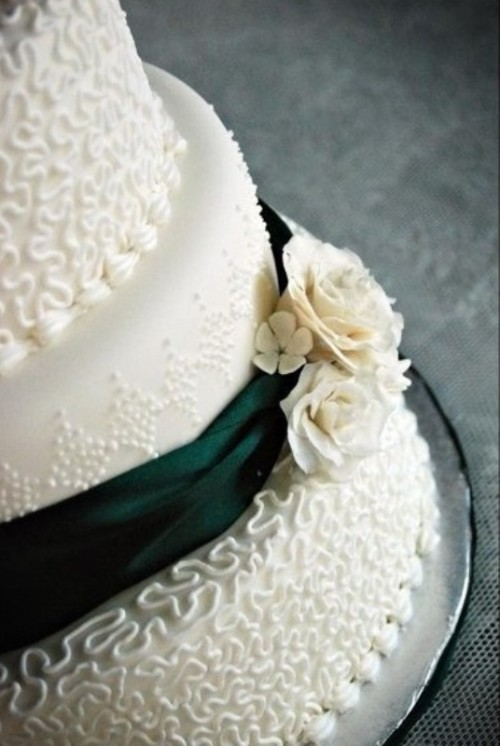 a textural white wedding cake decorated with green ribbons and sugar flowers