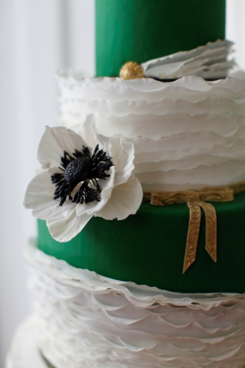 a white ruffle and sleek emerald wedding cake with gold touches and a sugar bloom