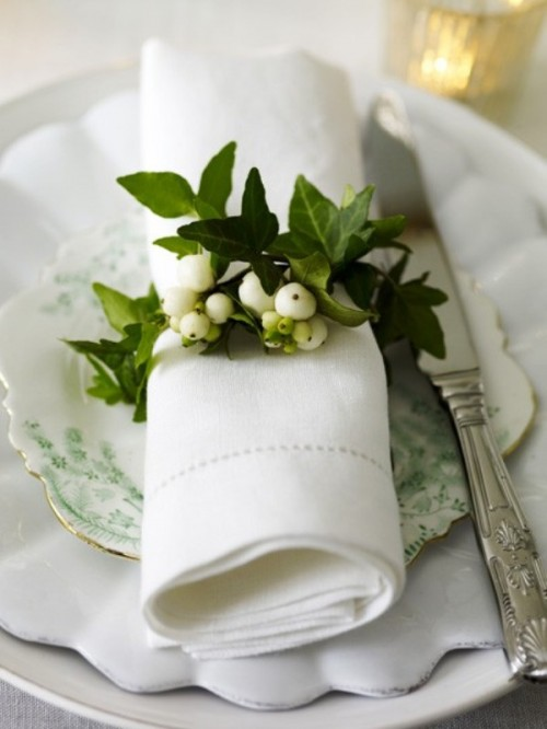 a napkin ring of greenery and white berries is a fresh and cute idea for any tablescape