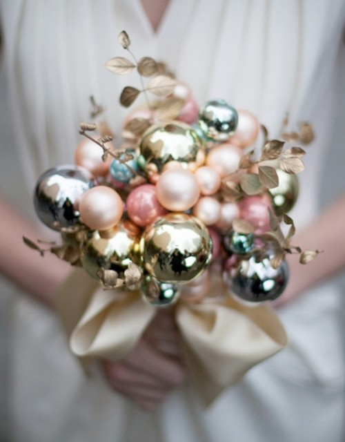 a holiday wedding bouquet fully made of Christmas ornaments and gold foliage plus a neutral ribbon for a New Year or Christmas bride