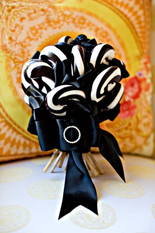 a Halloween weding bouquet made of black and white candy canes and accented with a black ribbon bow