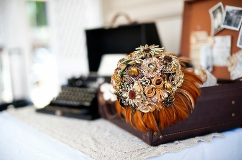 a gorgeous wedding bouquet of brooches and rust colored feathers for a steampunk bride