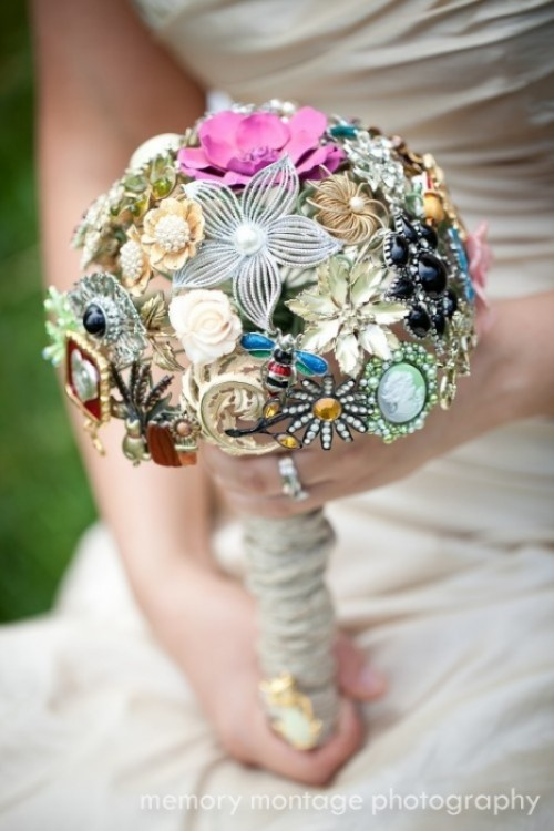 a chic and bold vintage brooch and button wedding bouquet with a wrap is a unique idea