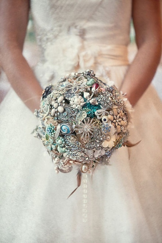 a bright and shiny vintage brooch wedding bouquet with feathers is a stylish and cool idea to DIY