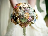 a colorful brooch and button wedding bouquet with a neutral wrap is a bright and bold idea