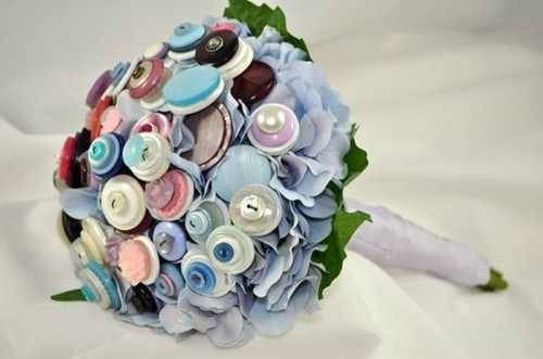 a wedding bouquet made of colorful and pastel colored buttons with leaves of paper and a neutral wrap