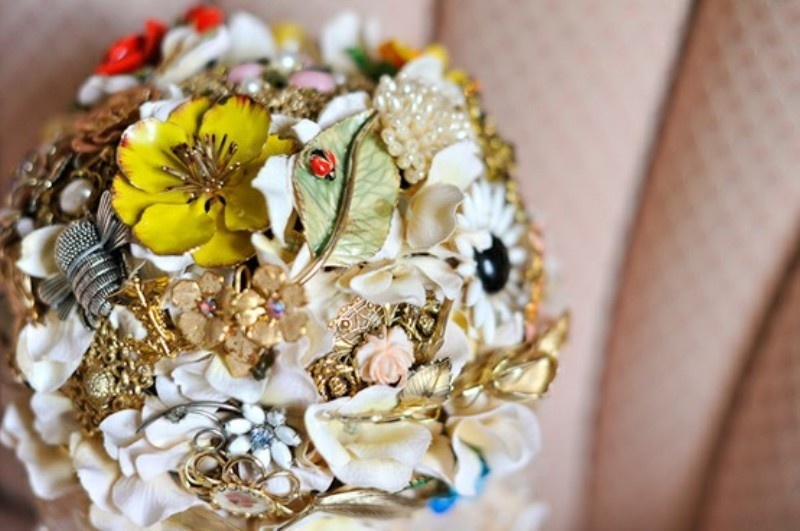 a bright and colorful brooch wedding bouquet in various colors with leaves and flowers is a refined option for a bride
