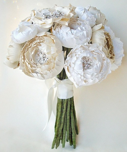 a whole bouquet of paper blooms with brooches and a white wrap is a stylish and bright idea