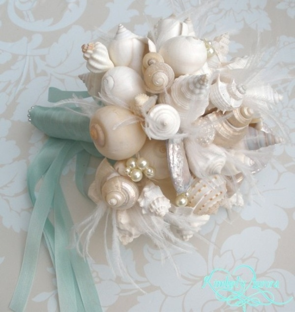 a beach or coastal wedding bouquet fully made of seashells and aqua colored ribbons with a bow