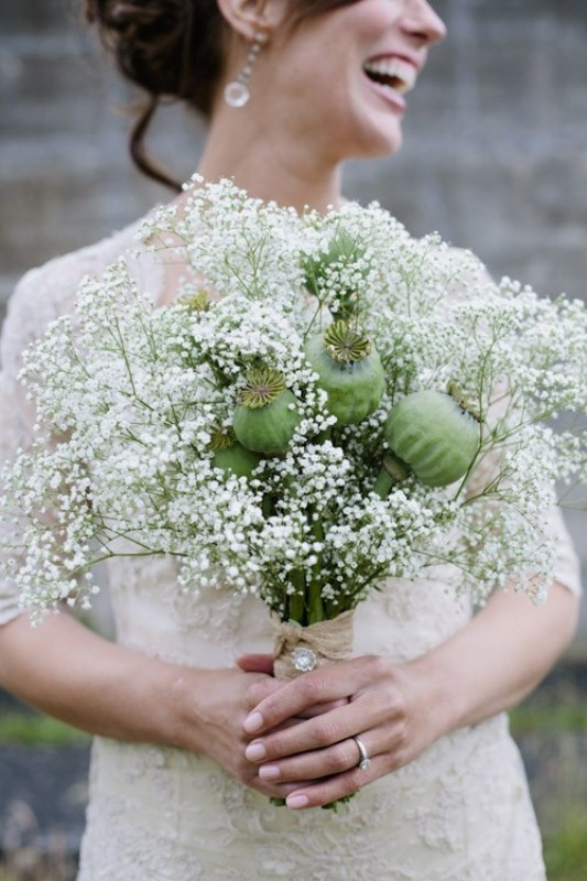a unique wedding bouquet with baby's breath and some seed pods is a creative idea