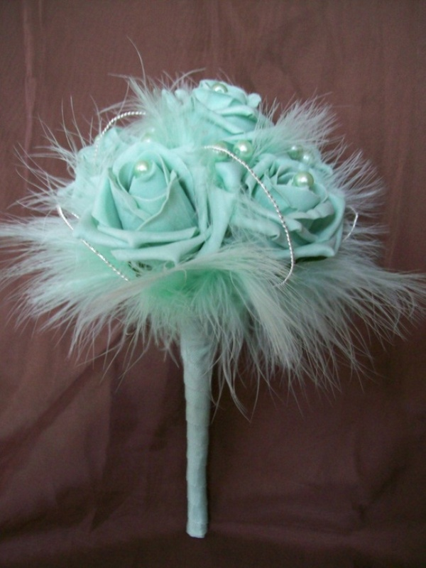 a mint green wedding bouquet of fabric blooms, pearls and feathers is a chic idea