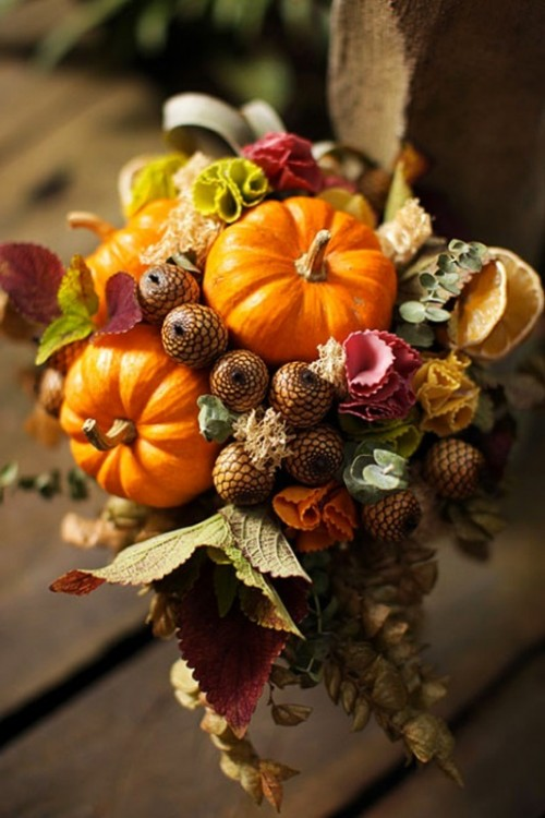 a rustic fall wedding bouquet with pumpkins, leaves, acorns and even fruit plus dried foliage