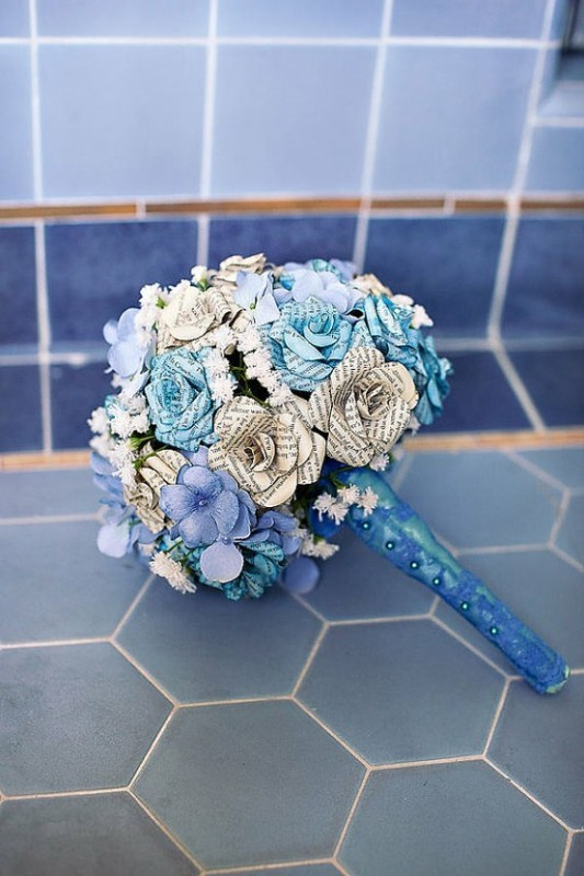 paper and fabric faux flowers in blue shades with a blue wrap with buttons is refined and chic