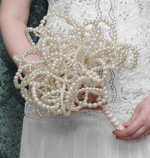 a wedding bouquet fully made of pearls is a very feminine and unexpected idea