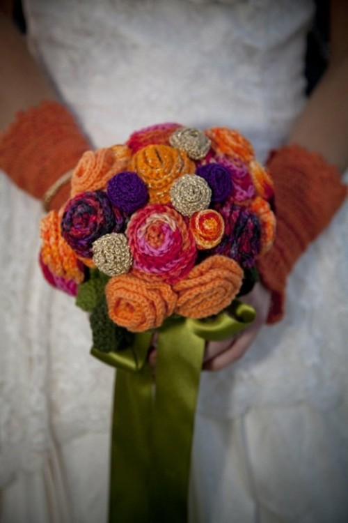 a colorful and bright knit flower wedding bouquet with green silk ribbons and matching mittens