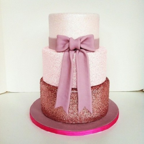 a cute pink glitter wedding cake with a lighter and a darker tier, with a large pink sugar bow is wow