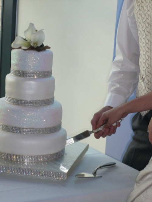 a white and silver glitter wedding cake with fresh blooms and greenery on top is a very glam and refined idea to rock